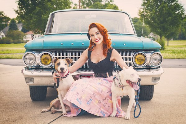 pit bull in a blue car with a pinup girl
